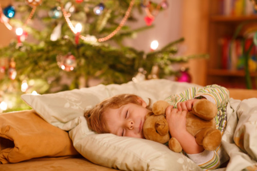 Little cute blond boy sleeping under Christmas tree and dreaming of Santa at home, indoors